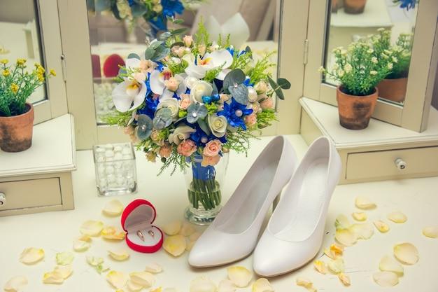 テーブルの上の花瓶に立っているウェディングブーケ。バラの花びらの靴と指輪。