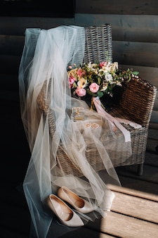 Wedding bouquet, veil and shoes of the bride are on a chair.