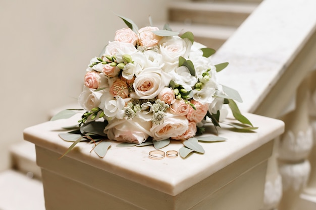 Wedding bouquet and wedding rings on a marble countertop