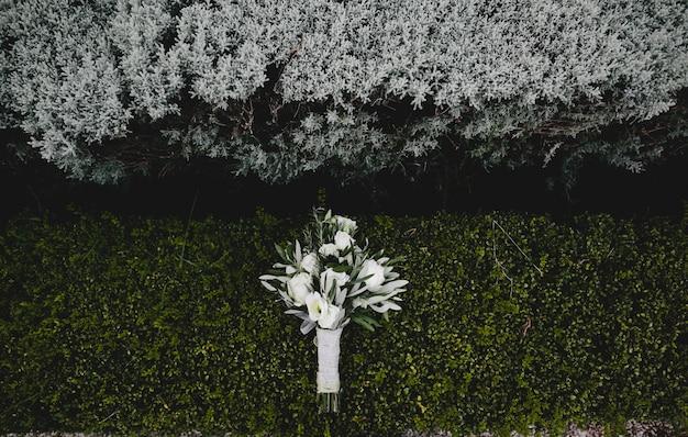 Wedding bouquet of white flowers lies on green bush
