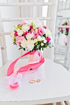 Wedding bouquet of white and pink roses and koalas on a chair.