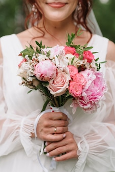 Wedding bouquet of white and pink roses and peonies in the hands of the bride on the background of a white dress