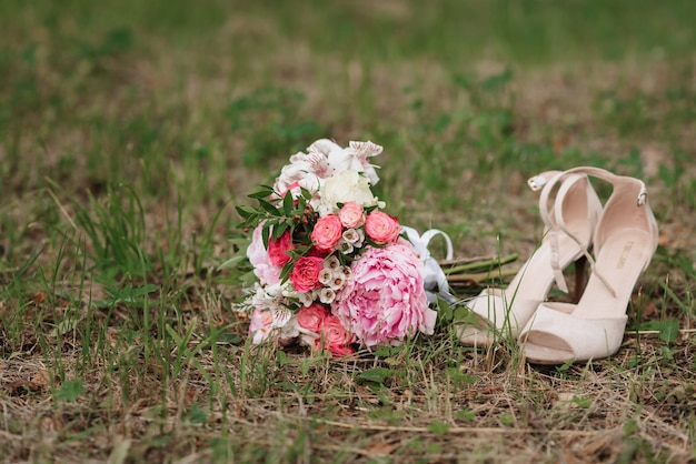 Wedding bouquet of white and pink roses and peonies with shoes lying on the grass