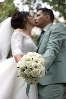 Wedding bouquet of white roses on the background of kissing newlyweds