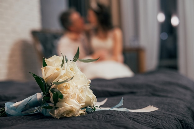 Wedding bouquet of white roses on the bed, blurred couple on background