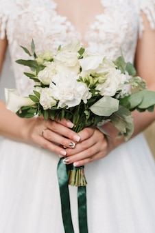 Wedding bouquet of white roses in the hands of the bride on the background of dress Premium Photo