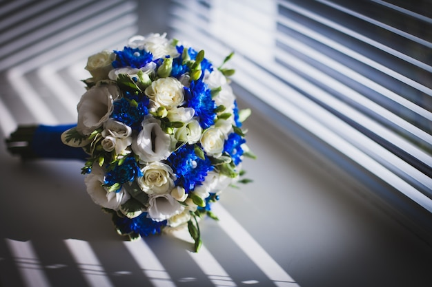 Wedding bouquet on the window with blinds