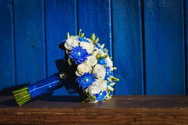 Wedding bouquet with blue and white flowers on a blue background