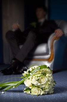 Wedding bouquet with the groom in the