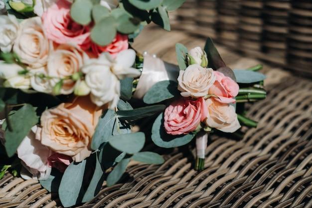 椅子とブートニア/ブートニエールに牡丹とバラのウェディングブーケ。結婚式の装飾