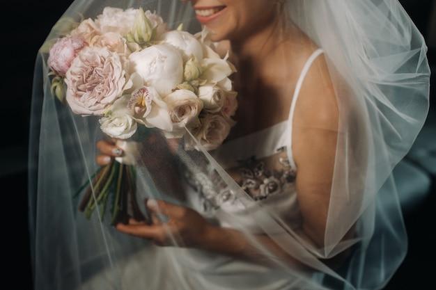 ベールの下で花嫁の手に牡丹のウェディングブーケ。花嫁の朝。
