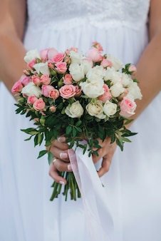 Wedding bouquet with pink and white roses in the hands of the bride