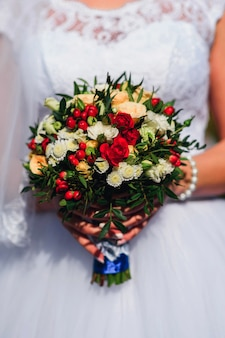 Wedding bouquet with red roses and daisies in the hands of the bride