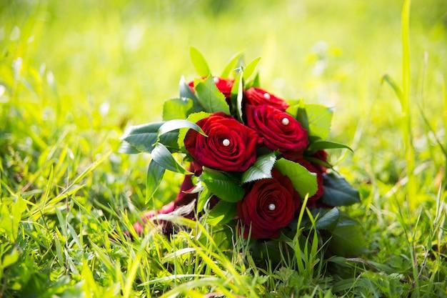 Свадебный букет с красными розами, лежащими на траве
