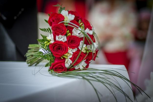 테이블에 빨간 장미와 웨딩 부케