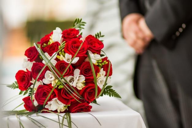 テーブルの上の赤いバラのウェディングブーケ