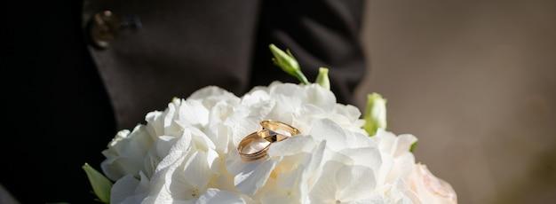 신혼 부부의 반지가 달린 웨딩 부케, 아름다운 카드