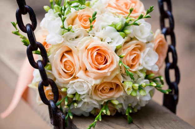 Wedding bouquet with roses and green branches on the swing