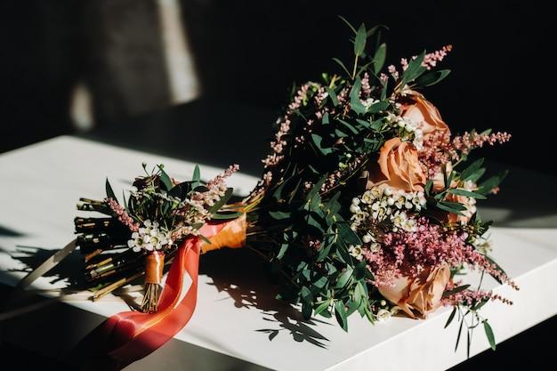 テーブルの上のバラとブートニアのウェディングブーケ。結婚式の装飾
