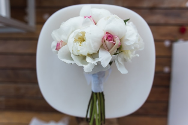 Wedding bouquet with roses and peonies lies on a white chair