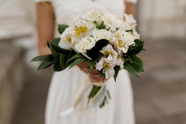 Свадебный букет с белыми розами и зелеными листьями. невеста в платье держит букет.