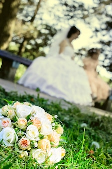Свадебный букет с белыми розами на траве
