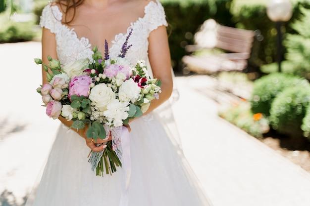 Свадебный букет из белых роз, пионов и зеленых листьев. невеста в платье держит букет.