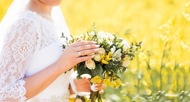 黄色い花のウェディングブーケ。手に花嫁の花束。
