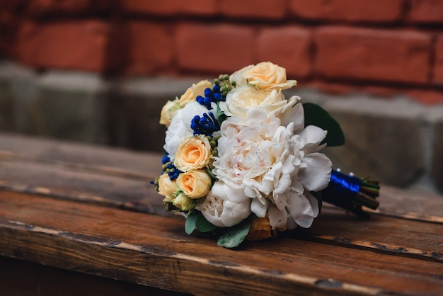 Wedding bouquet with yellow roses and white peonies