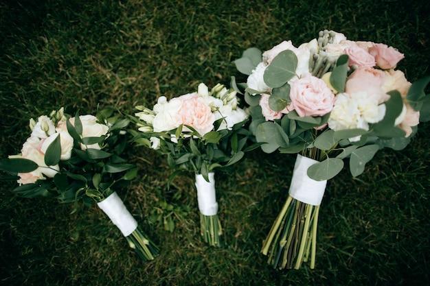 白とピンクのバラのウェディングブーケは緑の芝生に寝転んで