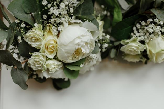 白いバラと白いテーブルの上のブライドメイドの緑のウェディングブーケ。花嫁の朝。結婚式のアクセサリー。セレクティブフォーカス