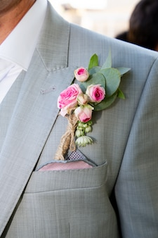 Wedding boutonniere on grey suit of the groom
