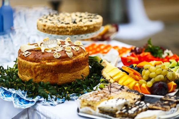 Wedding bread served on plate with greenery stands among plates