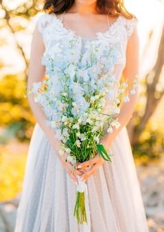 Wedding bridal bouquet of blue delphinium in the hands