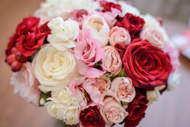 Свадебный букет невесты из красных, розовых и бежевых роз крупным планом