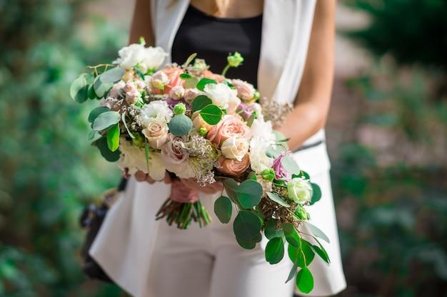 ウェディングプランナーの手にあるさまざまな色のバラとユーカリのクローズアップのウェディングブライダルブーケ