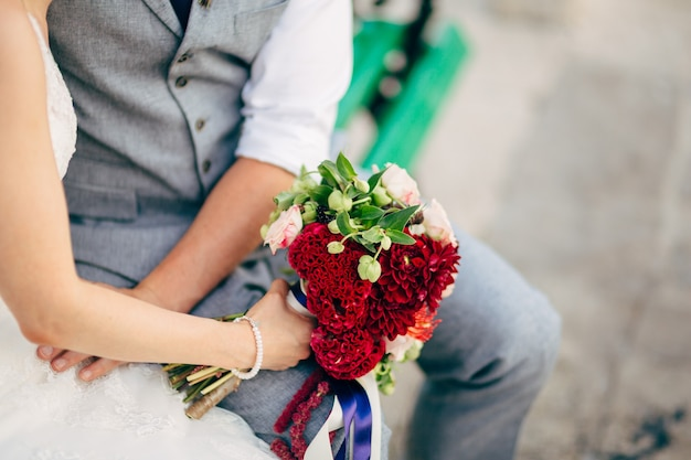 Wedding bridal bouquet of roses, celosia, proteus in the hands of the bride. wedding in montenegro, adriatic.