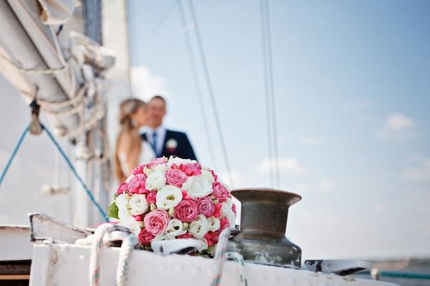 新郎新婦を背景にヨットにピンクと白のバラの結婚式のブライダルブーケ。結婚式のコンセプト