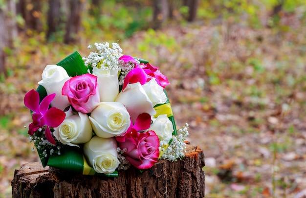 흰 난초, 장미, 데이지, 붉은 열매가 있는 웨딩 부케
