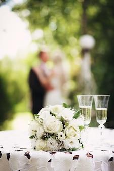 Свадебный букет невесты с белыми розами на столе в саду