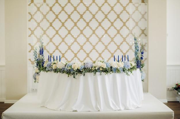 Свадебный стол жениха и невесты в президиуме украшен множеством цветов.