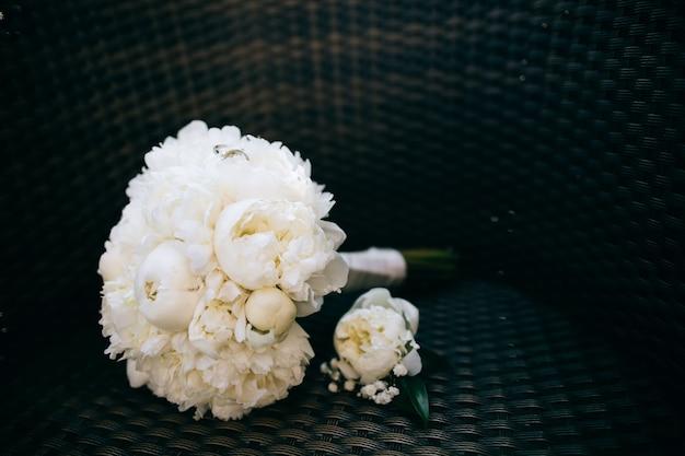 흰색 꽃과 신랑 boutonniere 어두운 배경에 누워 웨딩 신부 부케