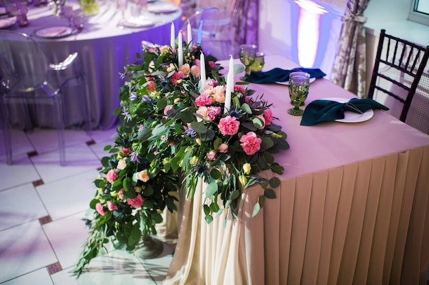 Wedding bride and groom table presidium decorated with a lot of flowers.