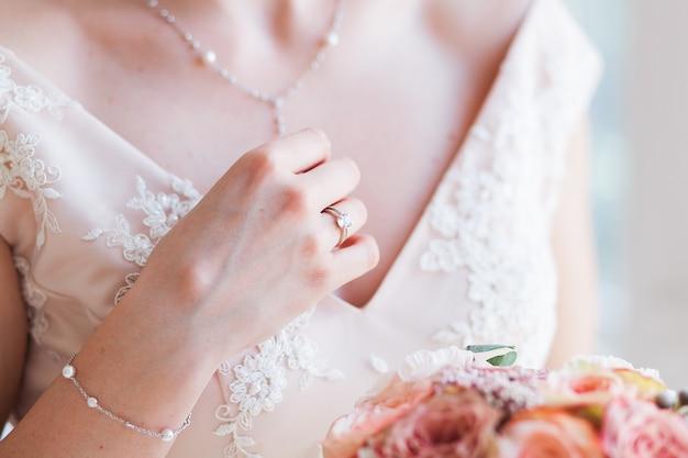 Wedding bride holding pink flower bouquet.