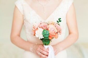結婚式の花嫁は、ピンクの花束を保持しています。
