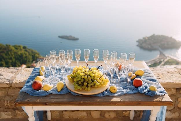 깨끗한 빈 샴페인 안경 웨딩 뷔페 테이블 흰색 포도와 과일 접시