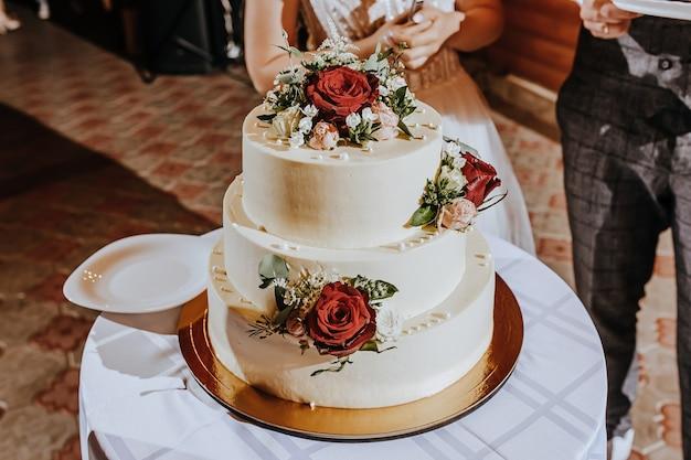 宴会でのウエディングケーキ。新婚夫婦がパーティーでケーキを切る