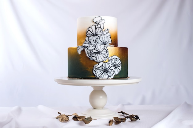 Wedding cake decorated gold, green gradient with hand drawn flowers
