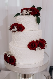 Torta nuziale decorata con rose rosse