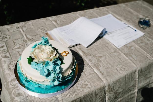 花のテーブルの上のウェディングケーキ。